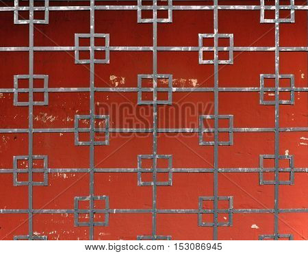 The square mesh pattern of black rusty metal on a background of red plaster wall.