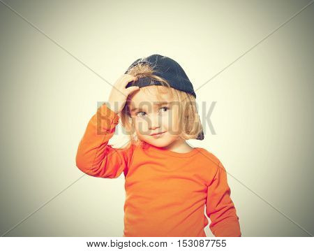 Little Funny Girl In Baseball Cap And Orange Blouse