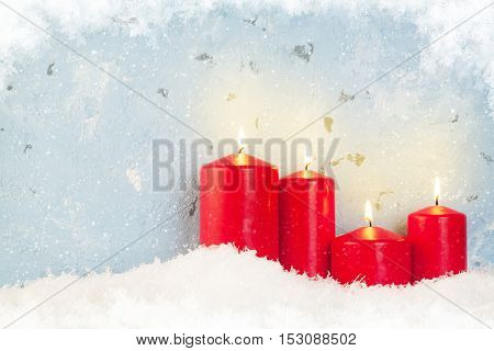 Christmas background with candles in snow in front of stone wall with copy space