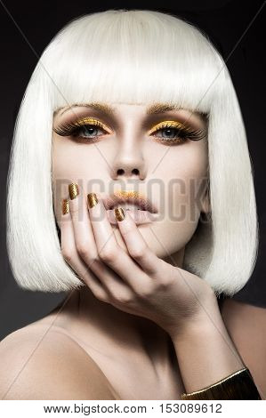 Beautiful girl in a white wig, with gold makeup and nails. Celebratory image. Beauty face. Picture taken in the studio.