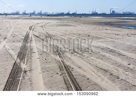 Tire tracks on the dutch beach and Rotterdam industry in the background