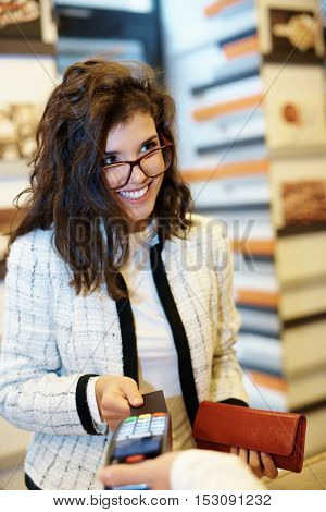 Young woman paying by credit card, smiling happy.