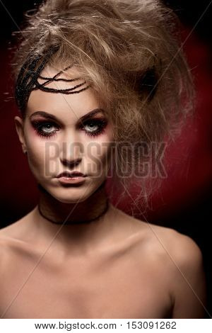 Decorative young woman in halloween makeup looking at camera.