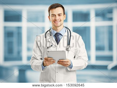 Professional male doctor with tablet on blurred hospital background. Gynecology concept.