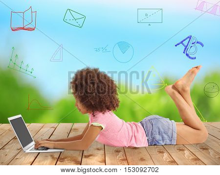 Cute little girl with laptop lying on wooden floor against blurred background. Diversity of school icons on background.