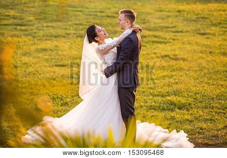 multi ethnic inter racial chinese british couple in wedding attire with a bouquet of flowers and greenery is in the hands against the backdrop of the field at sunset, the bride and groom