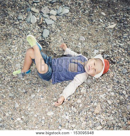 Fashion boy relaxing on a pebble beach