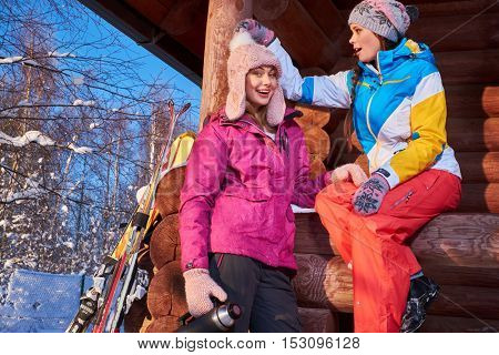 Happy girlfriends spend winter holidays at mountain cottage.