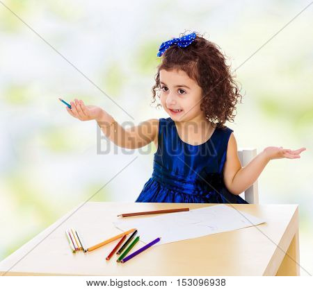 Adorable little girl in a blue dress drawing pencils . Girl sitting at the table.white-green blurred abstract background with snowflakes.
