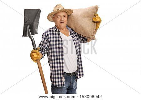 Joyful elderly farmer posing with a shovel and a burlap sack isolated on white background