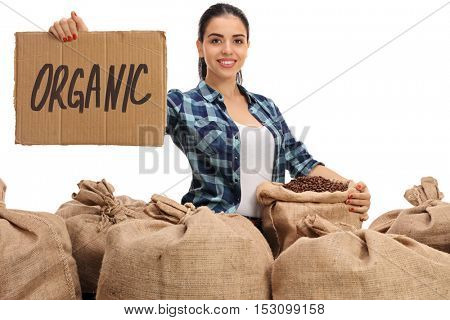 Cheerful female farmer posing with a pile of burlap sacks filled with coffee beans and a cardboard sign that says organic isolated on white background