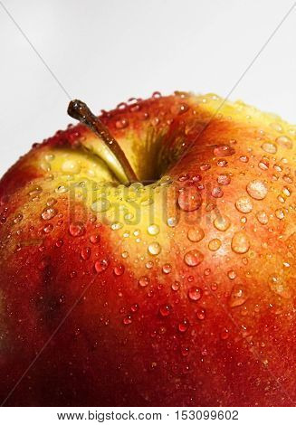 a juicy red apple with drops close-up.