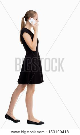 side view of a woman walking with a mobile phone. back view ofgirl in motion.  backside view of person.  Isolated over white background. The girl in a black dress talking on the phone sideways.