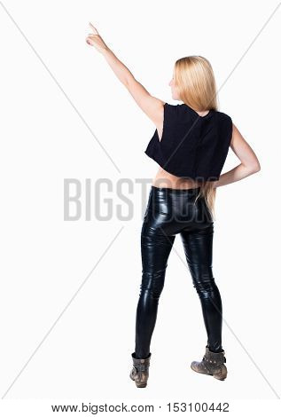 Back view of  pointing woman. beautiful girl. Rear view people collection.  backside view of person.  Isolated over white background. Blonde in leather jeans shows a hand up
