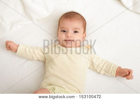 baby portrait lie on white towel in bed, yellow toned