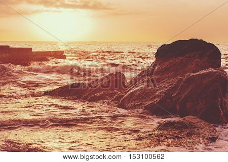 Sea wave splashing on rocks, natural holiday sunny vintage hipster seasonal background