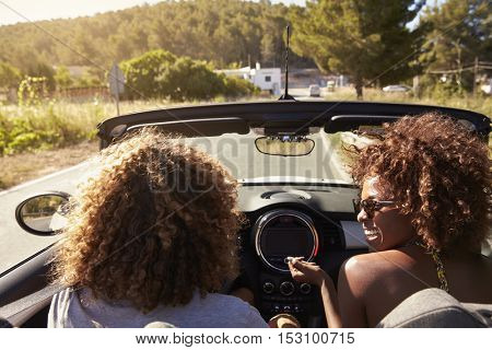 Happy young couple driving in an open top car, Ibiza, Spain