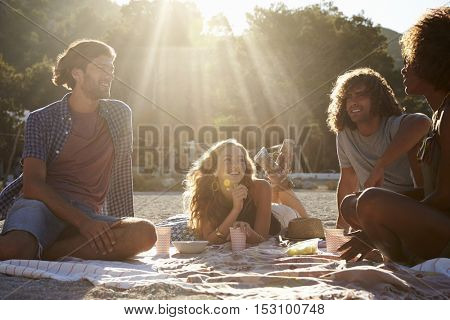 Four friends sitting in a row at a table by the sea, Ibiza