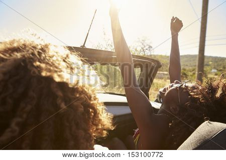 Young couple in an open top car, woman with arms raised