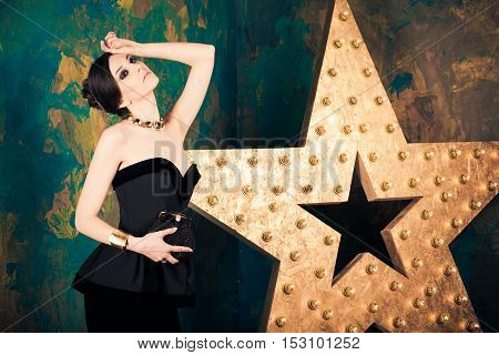 Dark haired woman in elegant black gown with clutch purse standing inside room with big decorating star