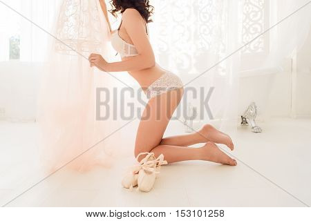 Nude ballerina standing on her knees near tutu. Desperate ballet dancer in white lingerie and with pointe shoes praying for success