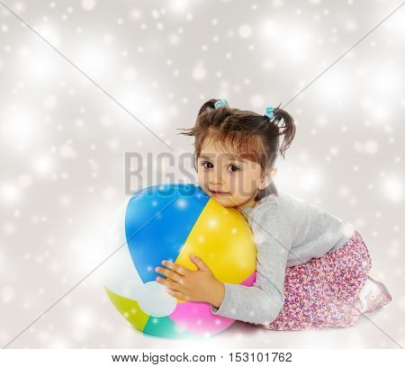 Cute little dark-haired girl with short pigtails on the head, hugging his big , inflatable, striped, vinyl ball.Gray background with round white snowflakes.