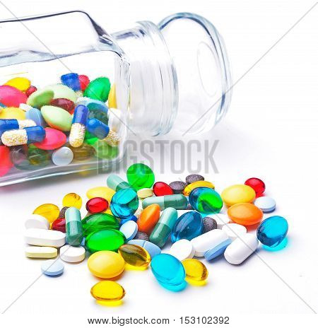 Colorful tablets with capsules on white background