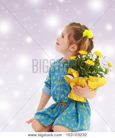 Pensive little girl in a short summer robe, holding a bouquet of yellow flowers.On new year purple background with white snowflakes.