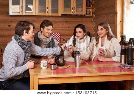 Best friends drinking hot tea in cosy kitchen at winter cottage.