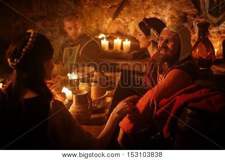 Medieval people eat and drink in ancient castle kitchen interior.