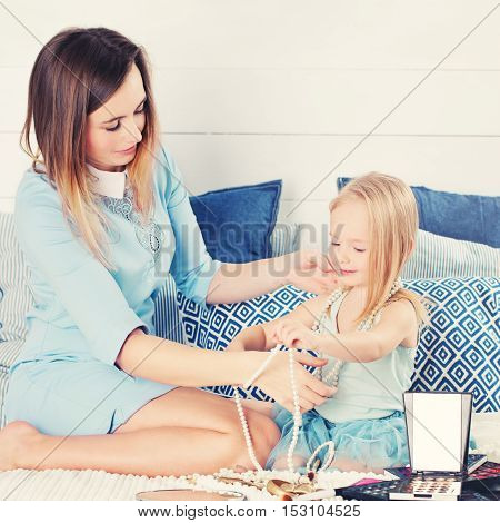 Happy family. Mother and daughter sitting on the bed in the bedroom and having fun