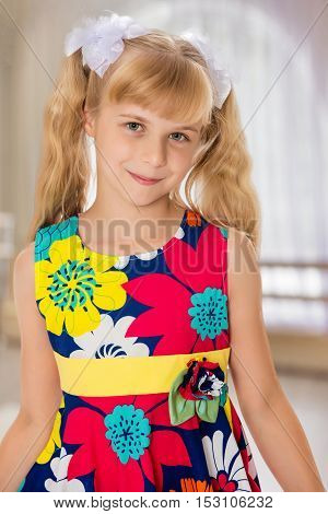 Sweet, adorable little girl with long blonde ponytails on her head tied with white bows. Close-up.In a room with a large semi-circular window.