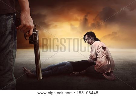Brave man with jeans pants holding gun looking at zombie eating flesh