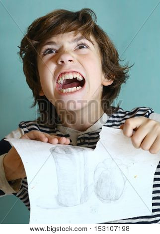 preteen school boy in rage tear ripping up his work