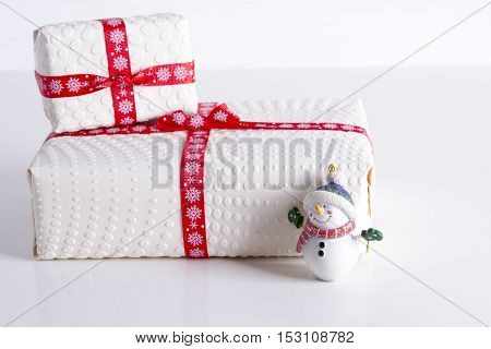 Two white gift boxes with polka dots with red ribbon and tree toy snowman