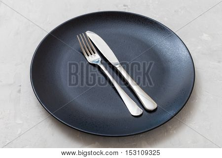 Black Plate With Parallel Knife, Spoon On Concrete