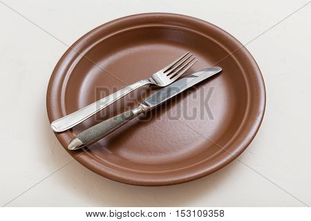 Brown Plate With Parallel Knife, Spoon On White