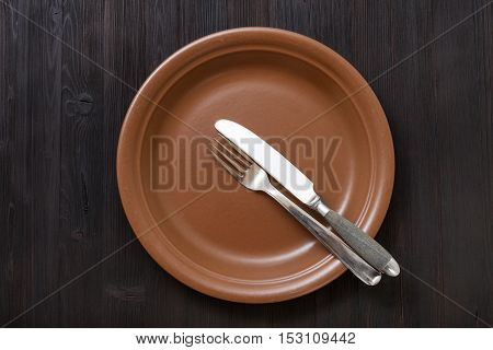 Top View Of Brown Plate With Flatware On Dark
