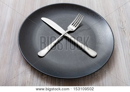 Black Plate With Crossing Knife, Spoon On Gray