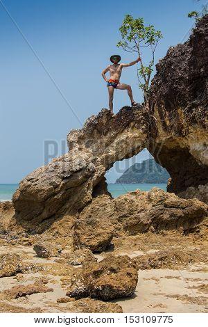 Sexy male vagabond beach bum taking a nap on a rock.