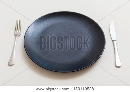 Black Plate With Knife, Spoon On White Plaster
