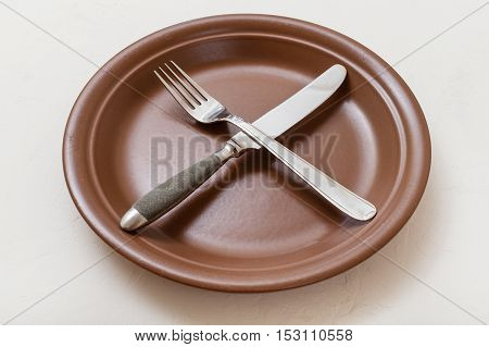 Brown Plate With Crossing Knife, Spoon On White