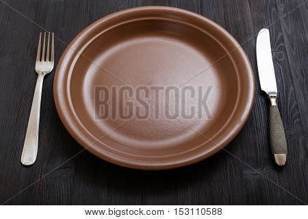 Brown Plate With Knife, Spoon On Dark Brown Table