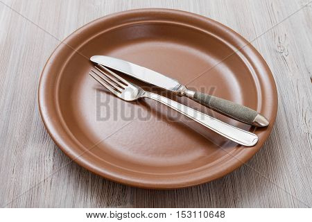 Brown Plate With Parallel Knife, Spoon On Gray