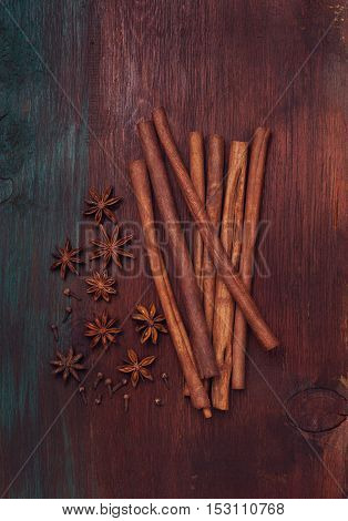 cinnamon sticks star anise and cloves on an old wooden background (dark top view)