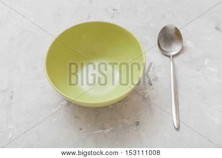 Green Bowl And Spoon On Gray Concrete Plate