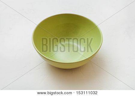 One Green Bowl On White Plaster