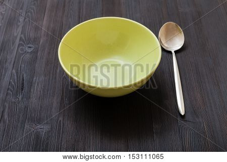 Green Bowl And Spoon On Dark Brown Board