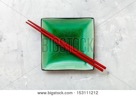 Above View Saucer With Chopsticks On Concrete
