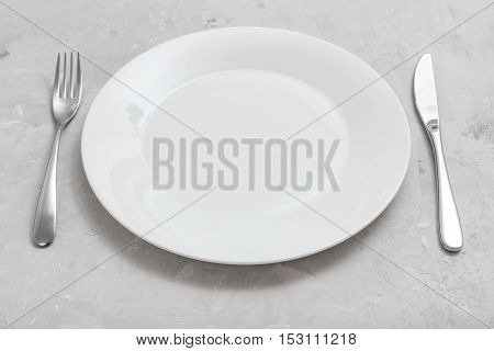 White Plate With Knife, Spoon On Gray Concrete